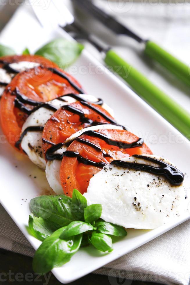 caprese salade met mozarella kaas, tomaten en basilicum op plaat foto