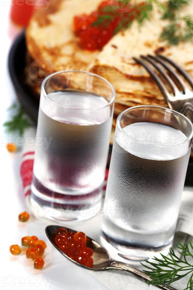 Russische wodka met pannenkoeken en rode kaviaar foto