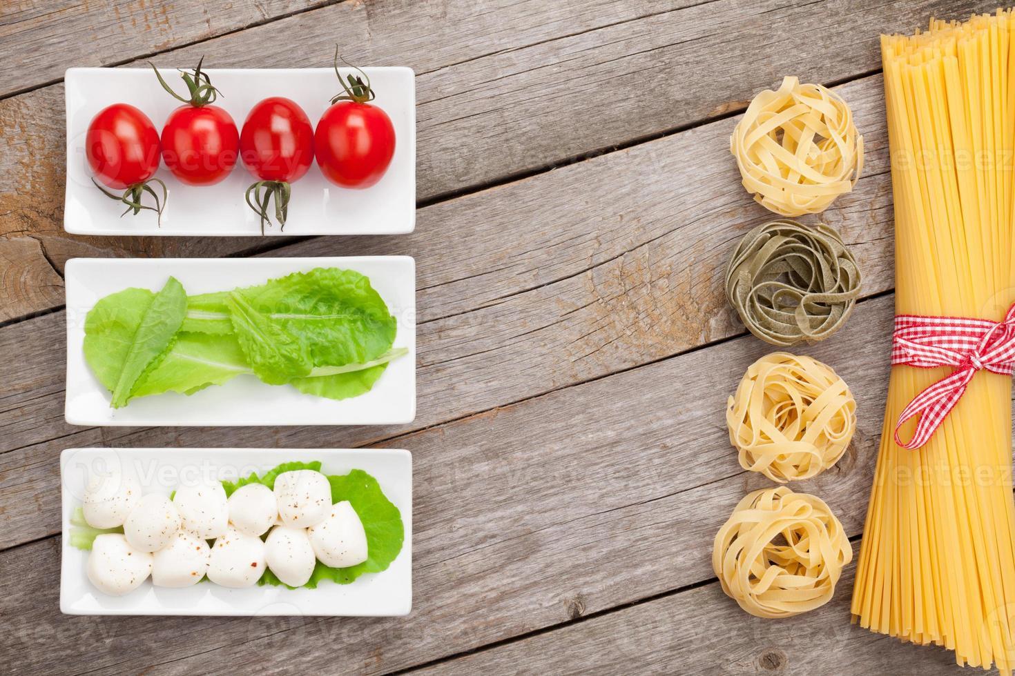 tomaten, mozzarella, pasta en groene slablaadjes foto