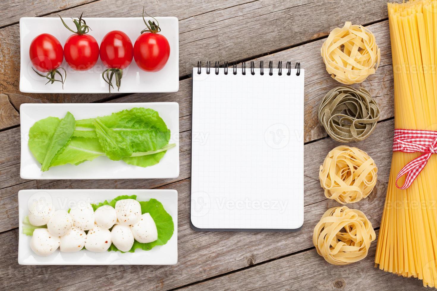 tomaten, mozzarella, pasta en groene slablaadjes met blocnote foto