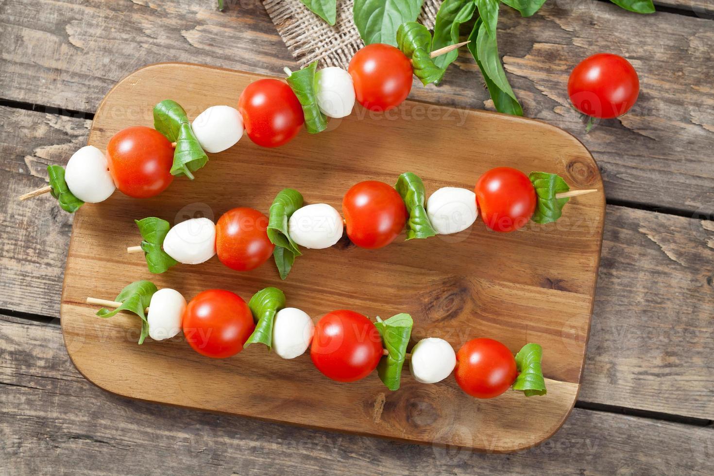 Italiaanse traditionele zelfgemaakte spiesjes met mozzarella tomaten en basilicum genoemd foto