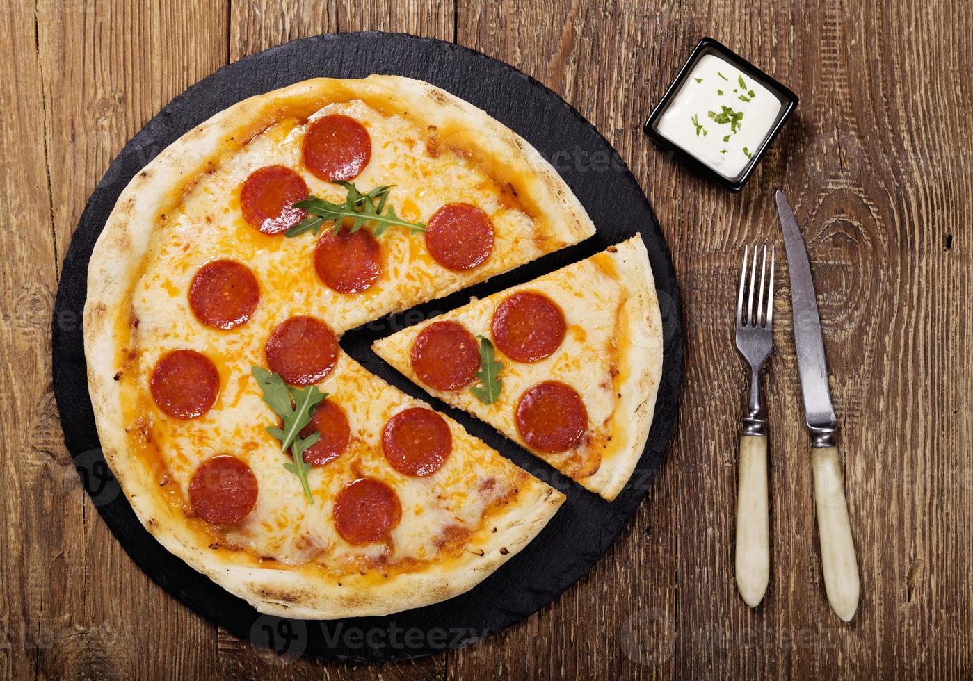 pizza peperoni op plaat foto
