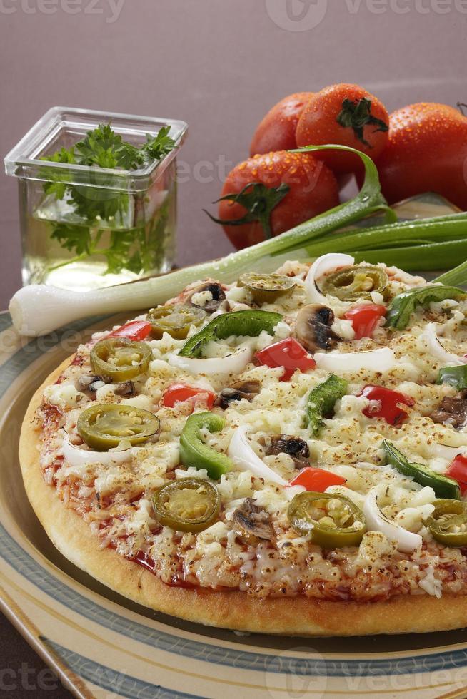 heerlijke pizza met groenten eromheen in setting. foto