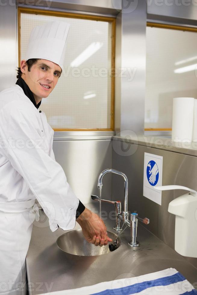 vrolijke chef-kok handen wassen foto