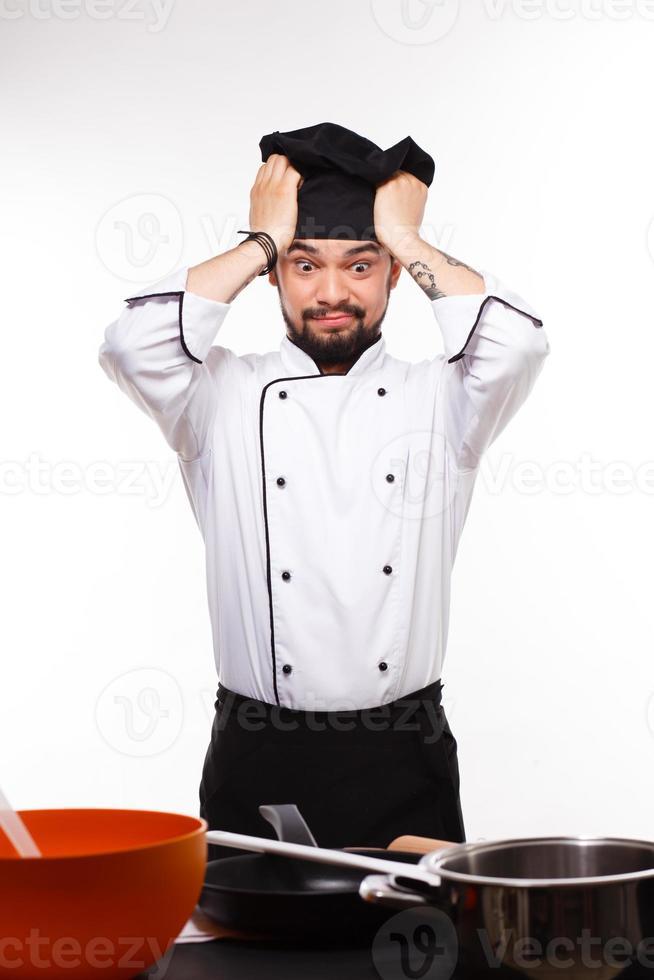 close-up portret van knappe kok op zoek naar een kleine pan foto