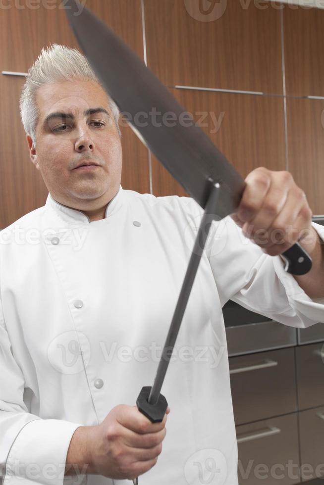 chef slijpen messen in commerciële keuken foto