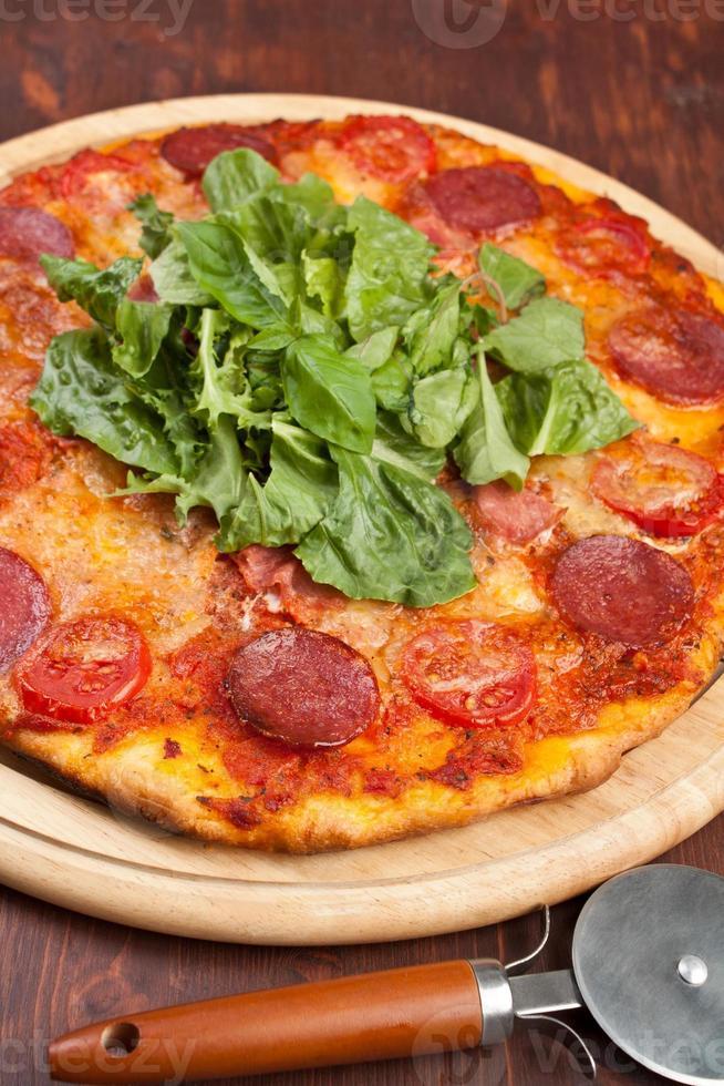 pizza met plakjes pepperoni, ham en champignons foto