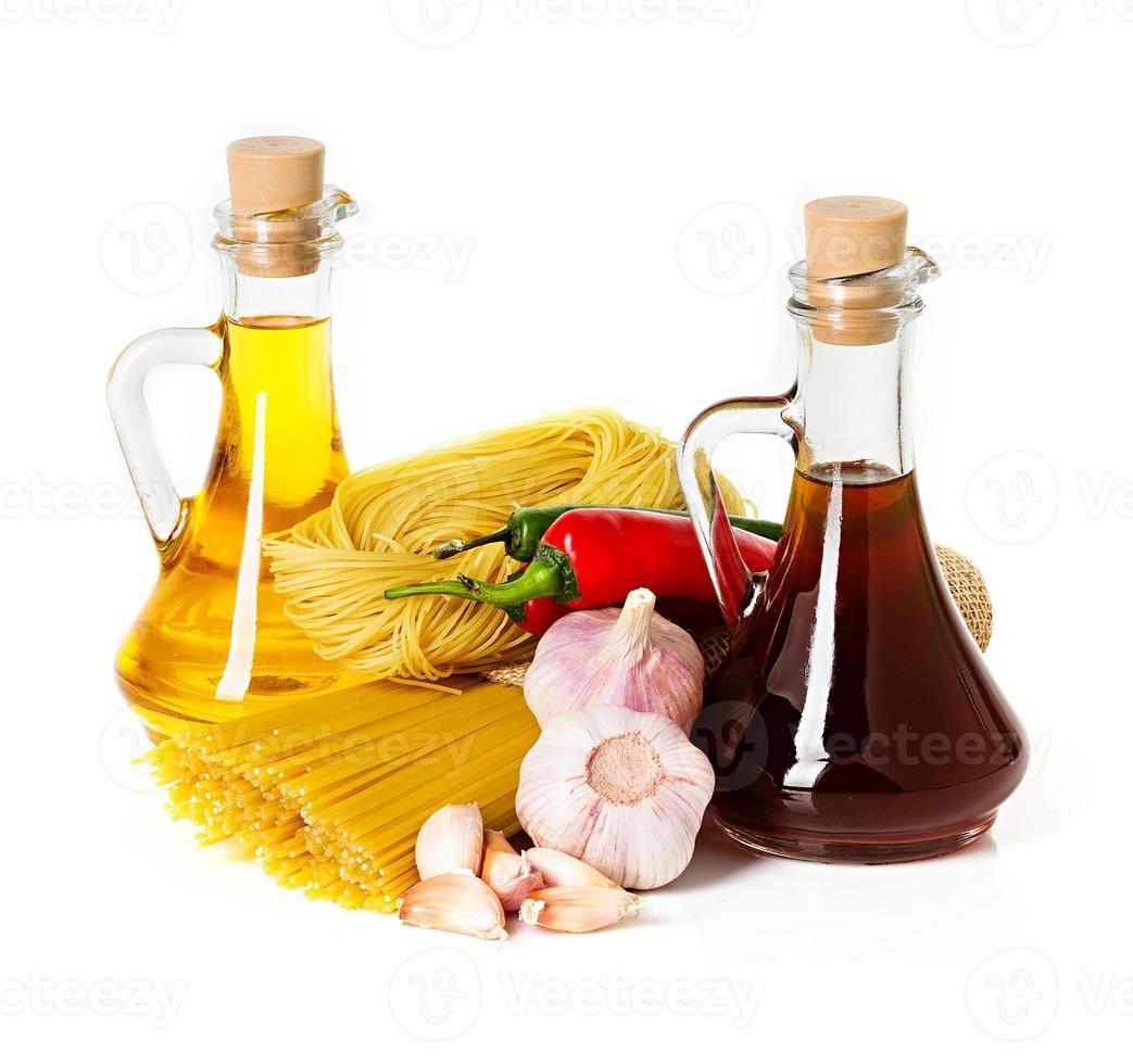 ingrediënten voor pasta. spaghetti, chili, olie, knoflook op wit wordt geïsoleerd foto