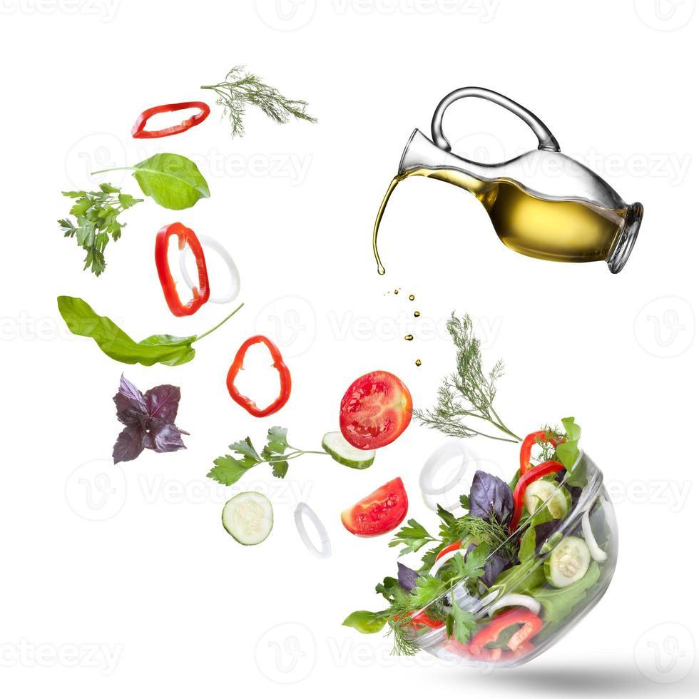 vallende groenten voor salade en olie geïsoleerd foto