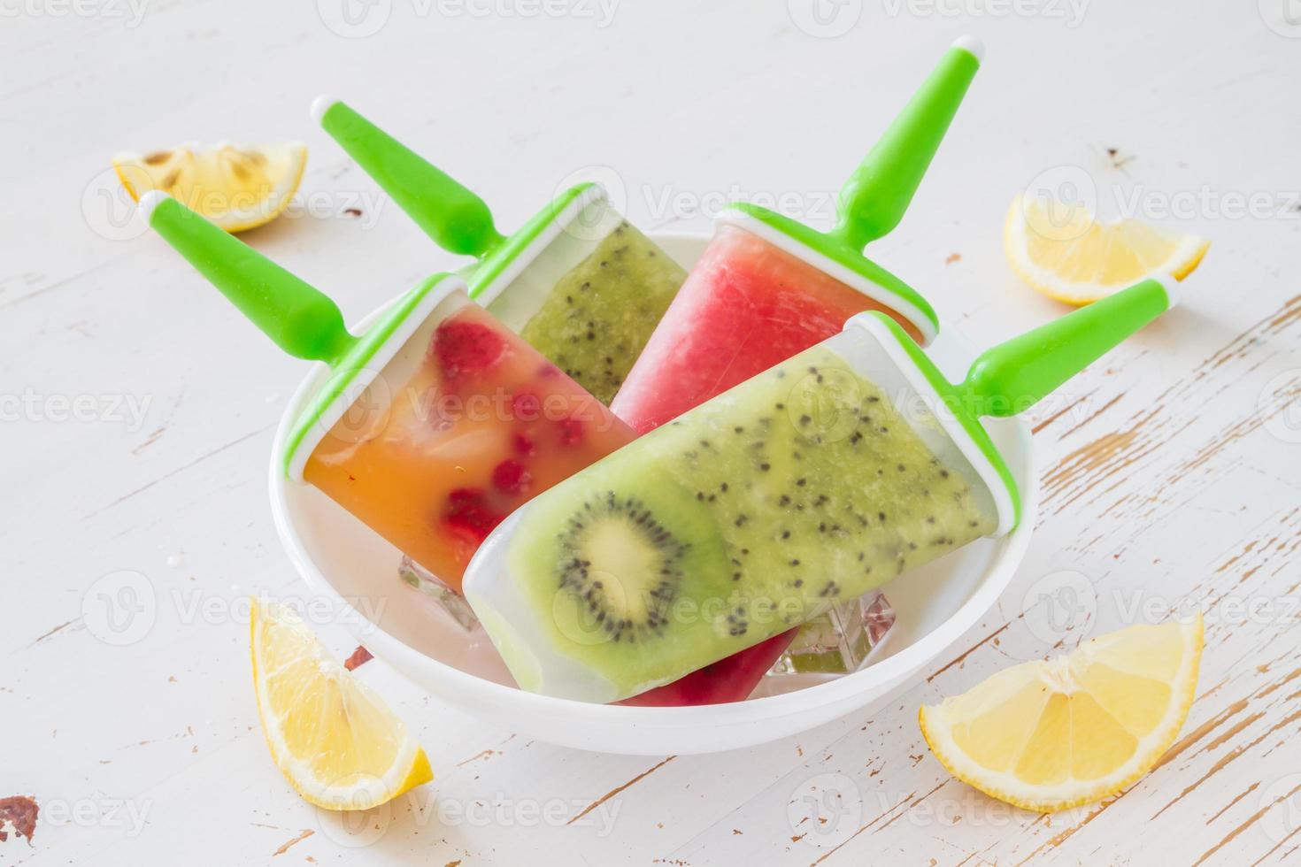 fruitijs springt met kiwi, watermeloen, bessen in witte kom foto