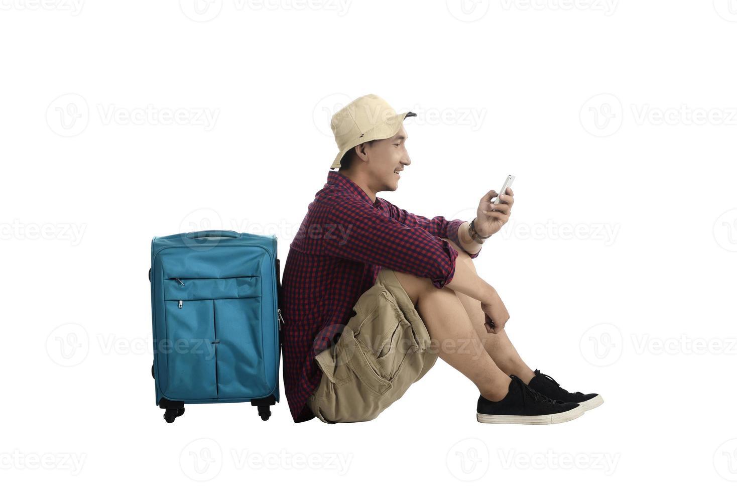 reiziger zit tegen een koffer en het gebruik van mobiel foto