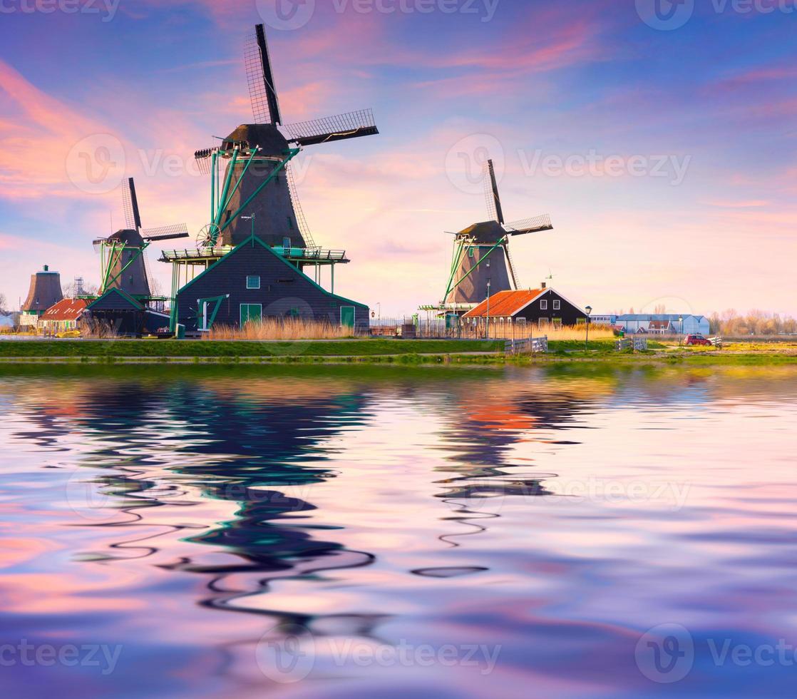 authentieke zaanse molens aan de waterkanaal in zaanstad. foto