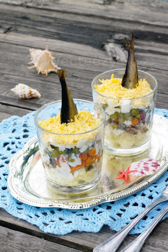 salade met sprot en groenten op een houten tafel foto