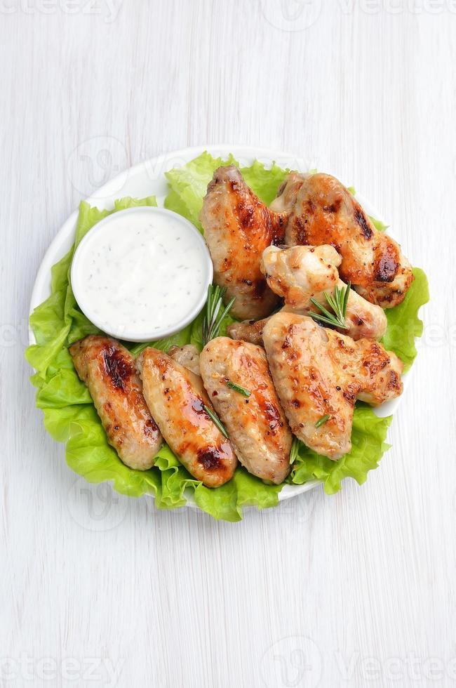 geroosterd kippenvleugelsvlees op slabladeren en saus foto