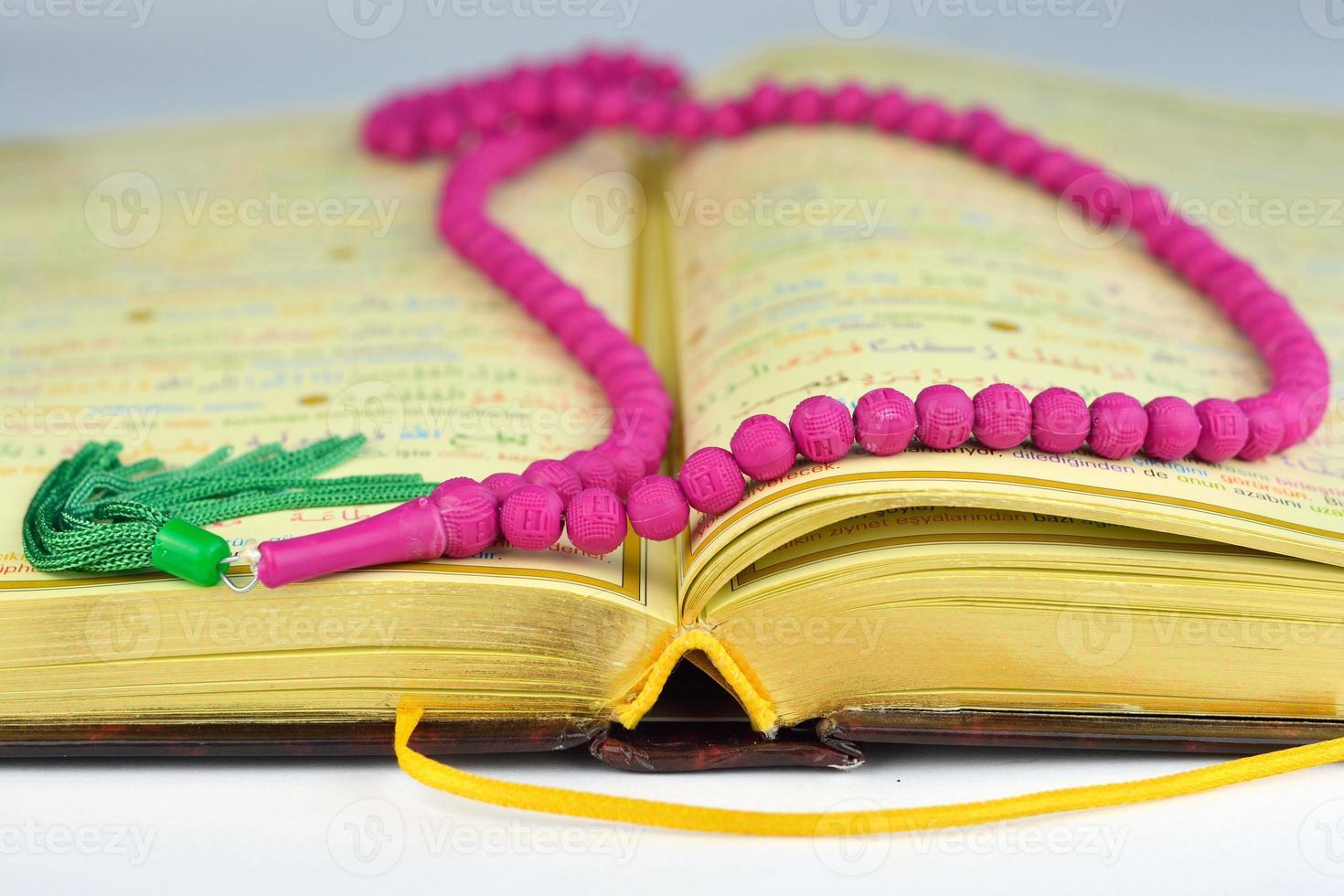 koran met rozenkrans bidparels in kleuren en gouden bladzijden foto