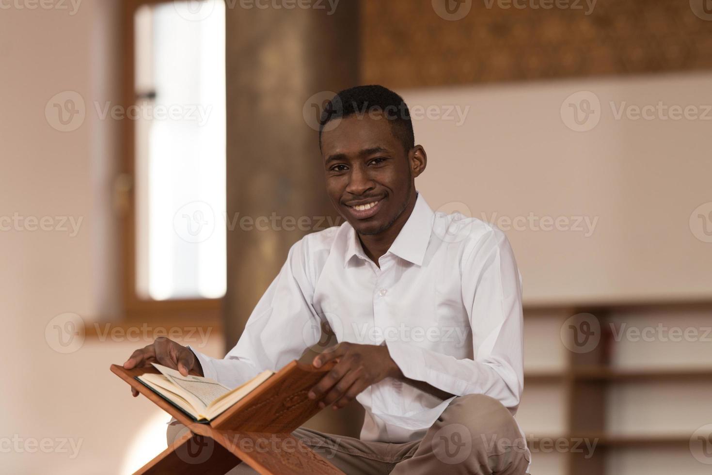 Afrikaanse moslim man leest heilige islamitische boek koran foto