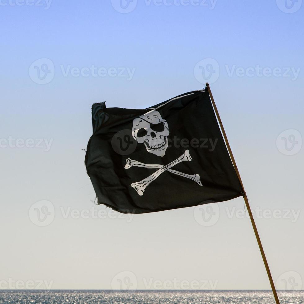 piraten vlag zwaaien met blauwe zee achtergrond foto