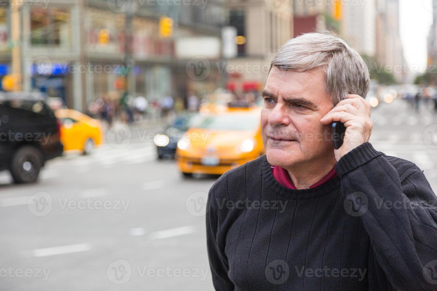 senior man praten op mobiele telefoon in New York foto