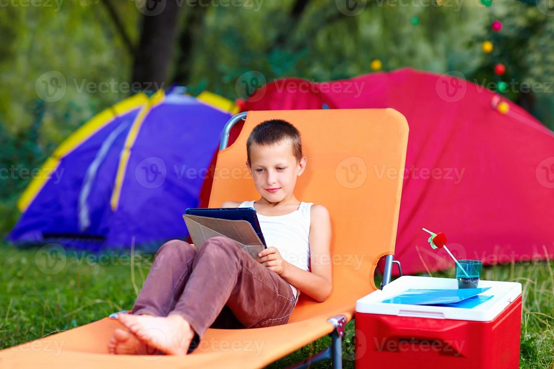 jonge jongen in zomerkamp, ontspannen met tablet foto