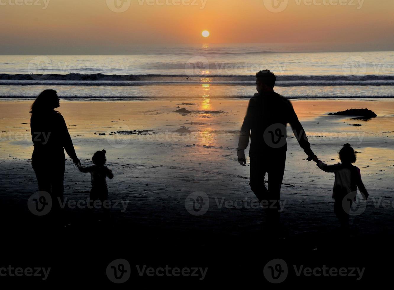 familie die een wandeling maakt bij zonsondergang westkust de vs foto