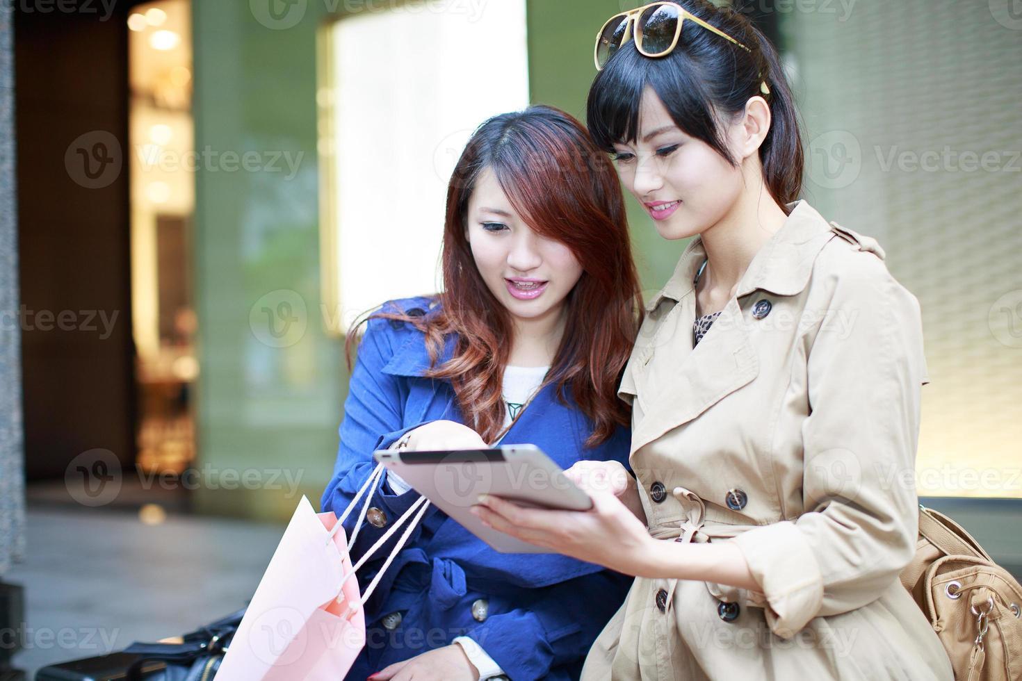 twee jonge vrouwen die samen winkelen foto