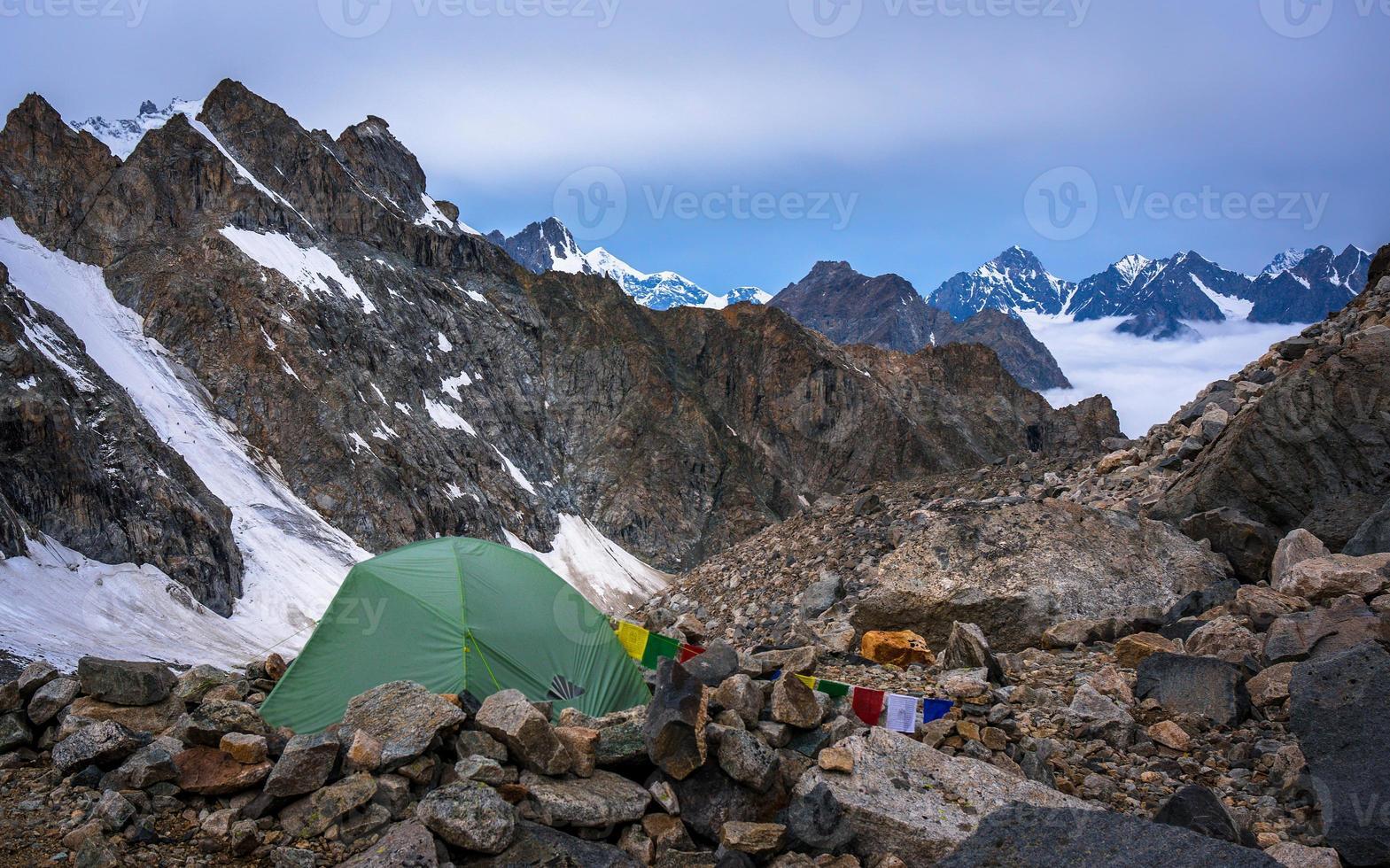 eenzame bergbeklimmers kamperen in zeer hoge besneeuwde bergen naast de gletsjer. foto