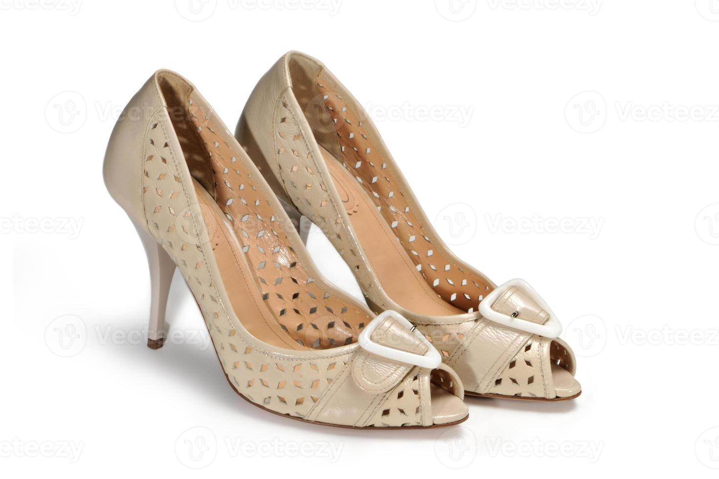 beige vrouwelijke schoenen op een witte achtergrond foto