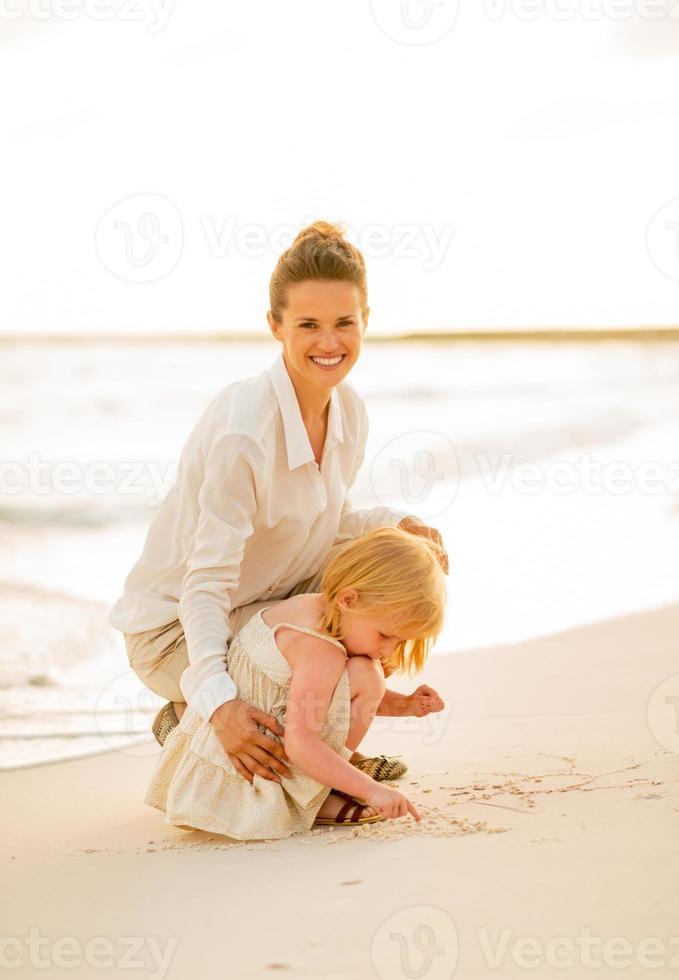 gelukkige moeder en babymeisje spelen op het strand foto