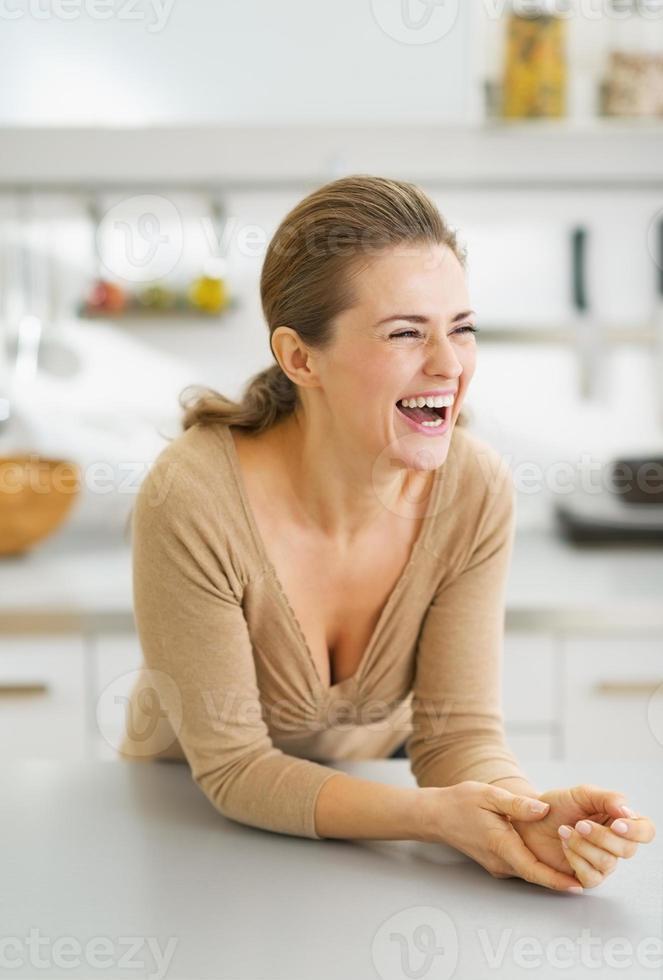 portret van lachende jonge huisvrouw in moderne keuken foto