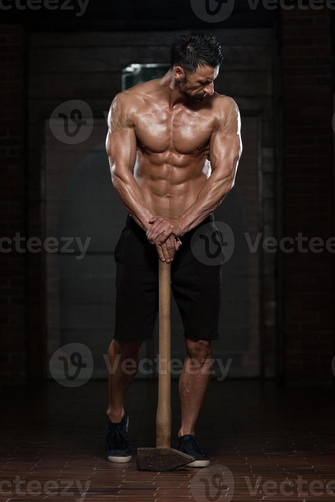man met hamer met zijn goed getrainde lichaam foto