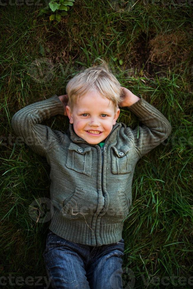 klein kind dat op gras en het glimlachen legt foto