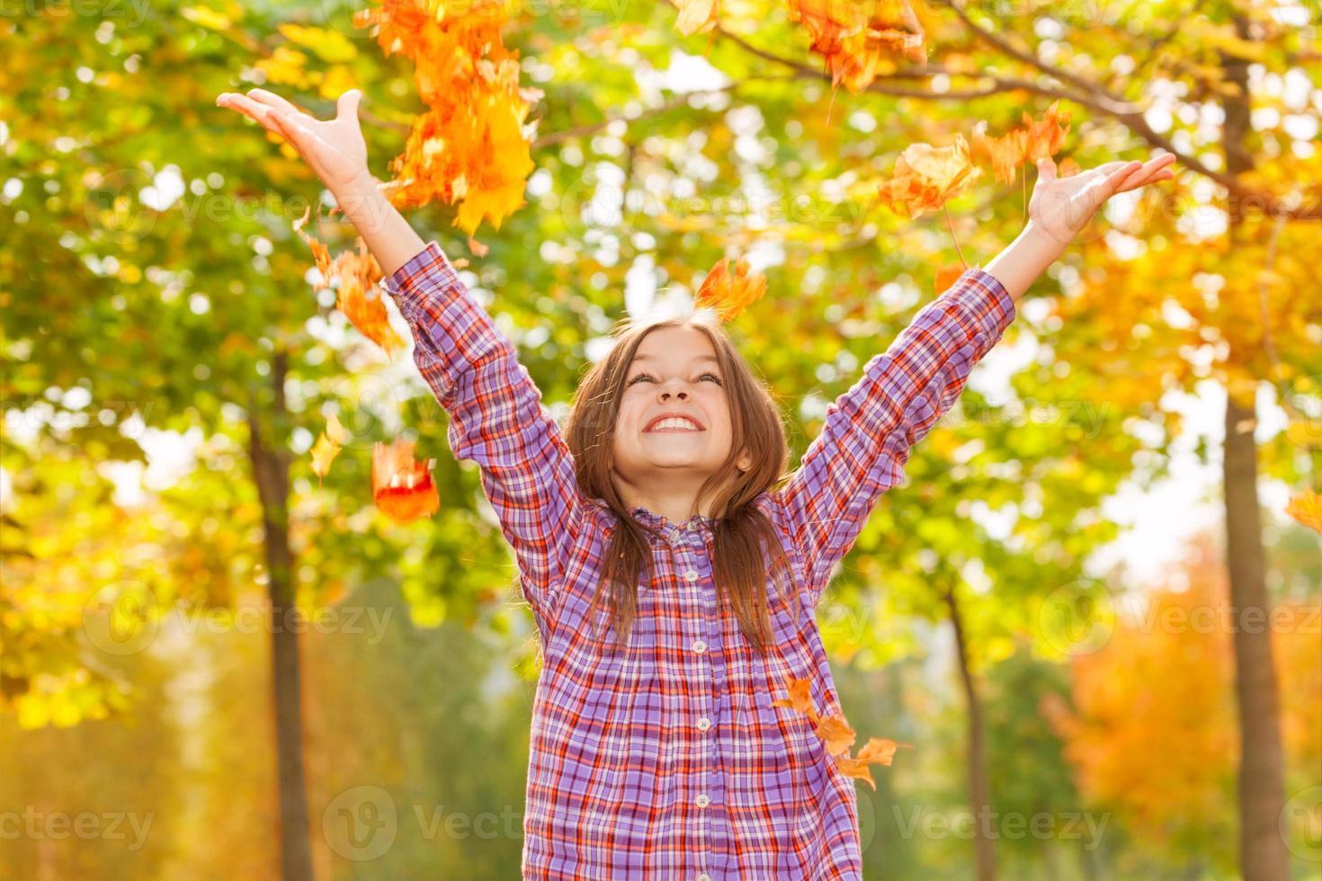 meisje gooien esdoorn oranje bladeren omhoog in herfst park foto