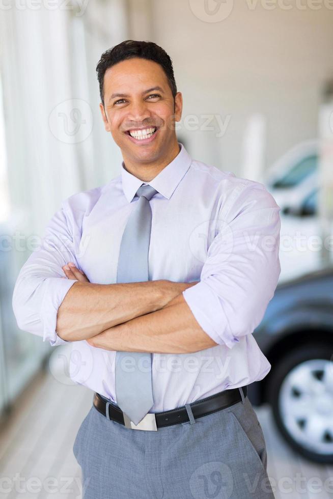 voertuig verkoper met armen gekruist in auto showroom foto