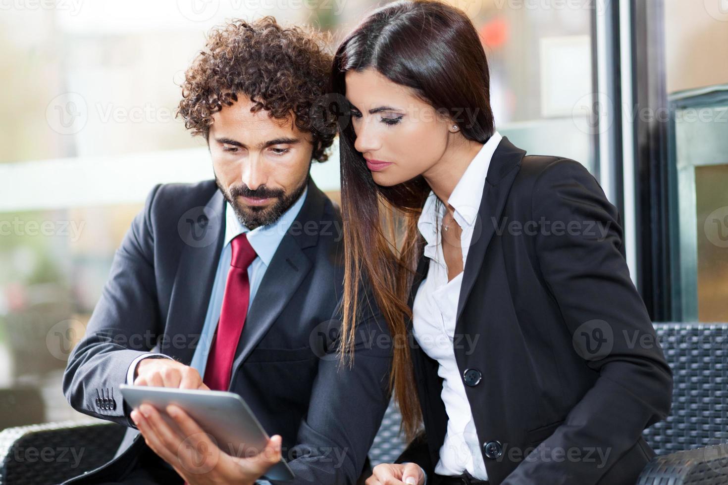 twee mensen uit het bedrijfsleven met behulp van een digitale tablet foto