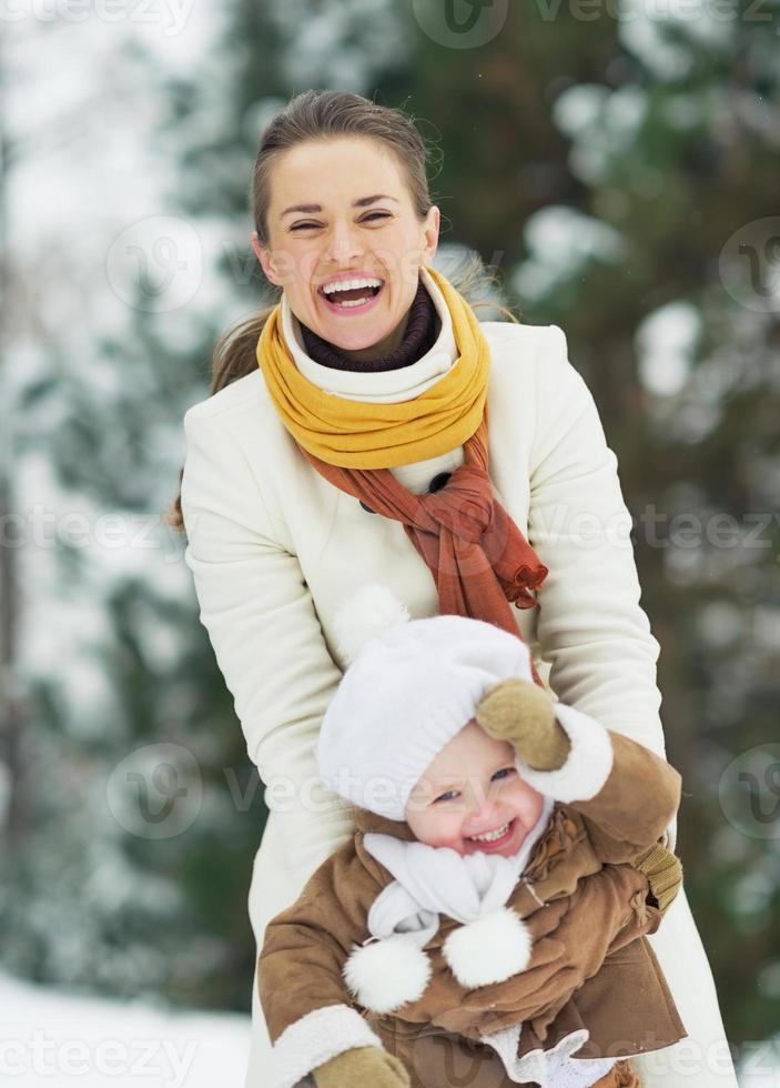 gelukkige moeder spelen met baby in winter park foto