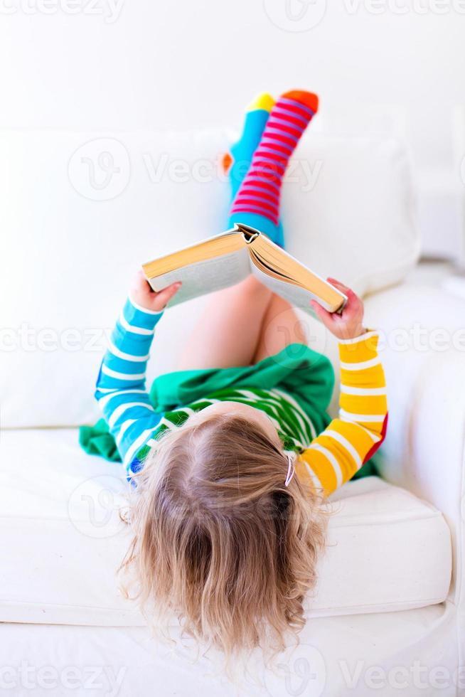 klein meisje het lezen van een boek op een witte bank foto