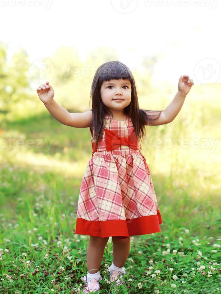 portret gelukkig schattig klein meisje kind draagt een rode jurk foto