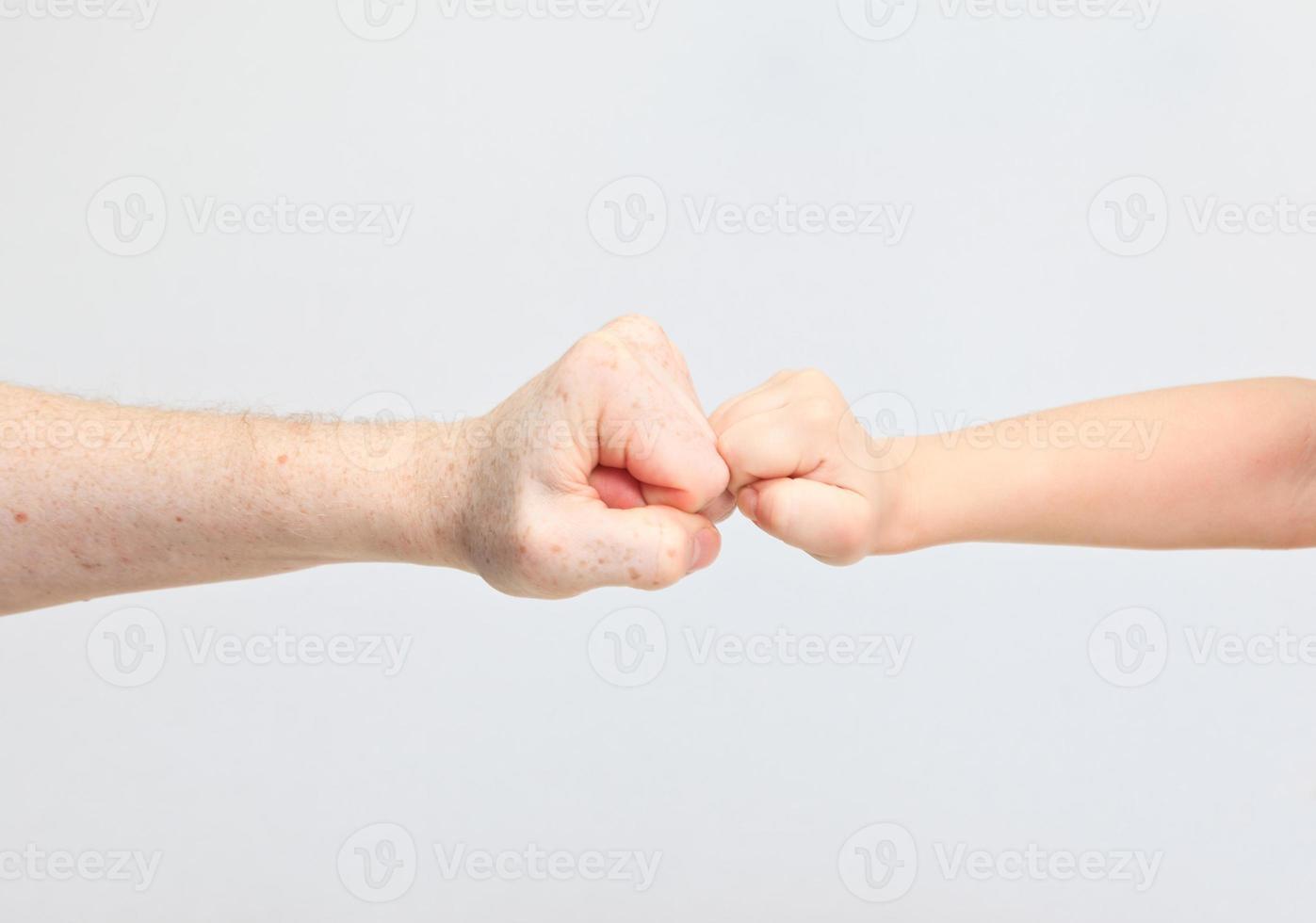 vuisten van een volwassene en een kind op wit foto