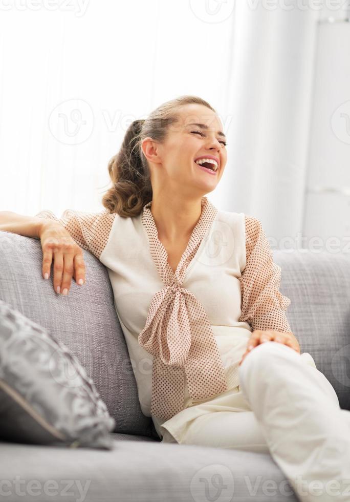 lachende jonge huisvrouw zitten in de woonkamer foto