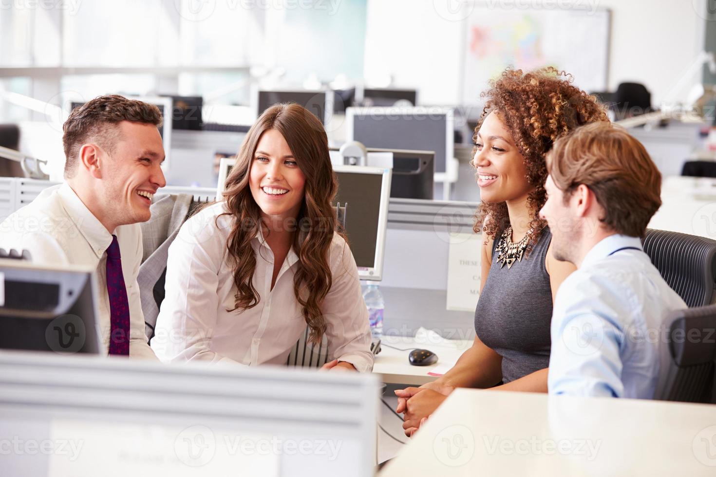 vier jonge kantoorcollega's in een informele teamvergadering foto