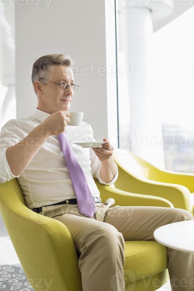 volwassen zakenman met koffie in de lobby op kantoor foto