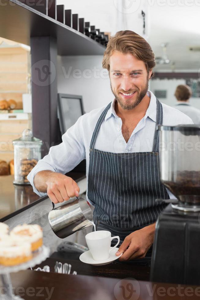 barista gieten melk in een kopje koffie foto