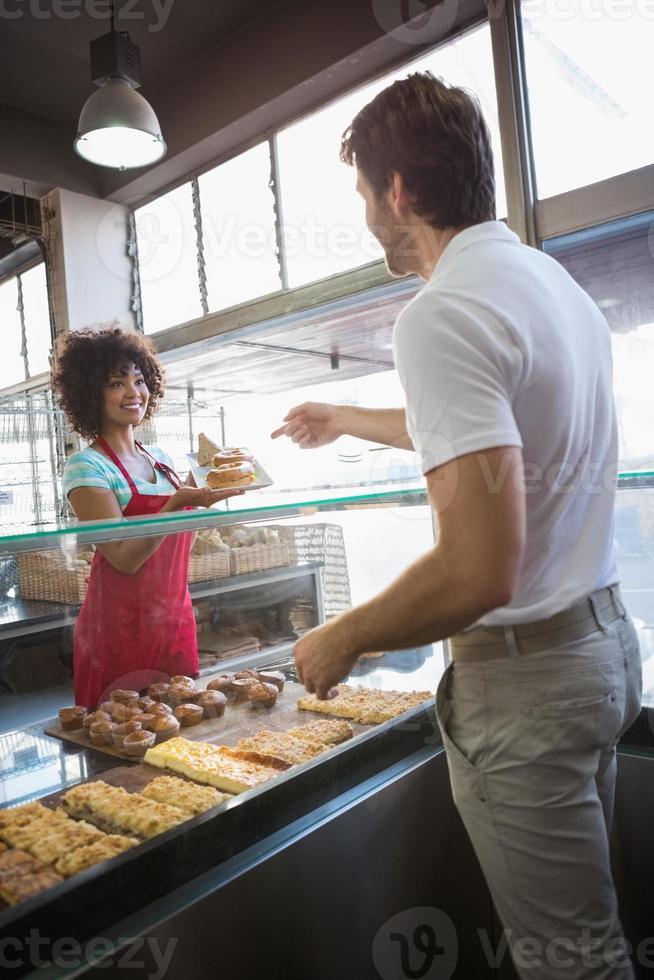 mooie serveerster die eten geeft aan klant foto