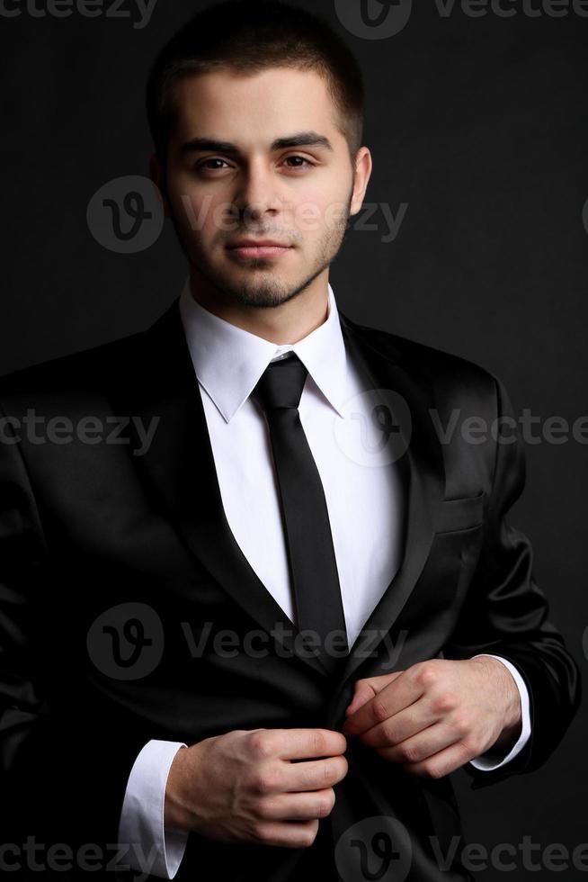 knappe jonge man in pak op donkere achtergrond foto
