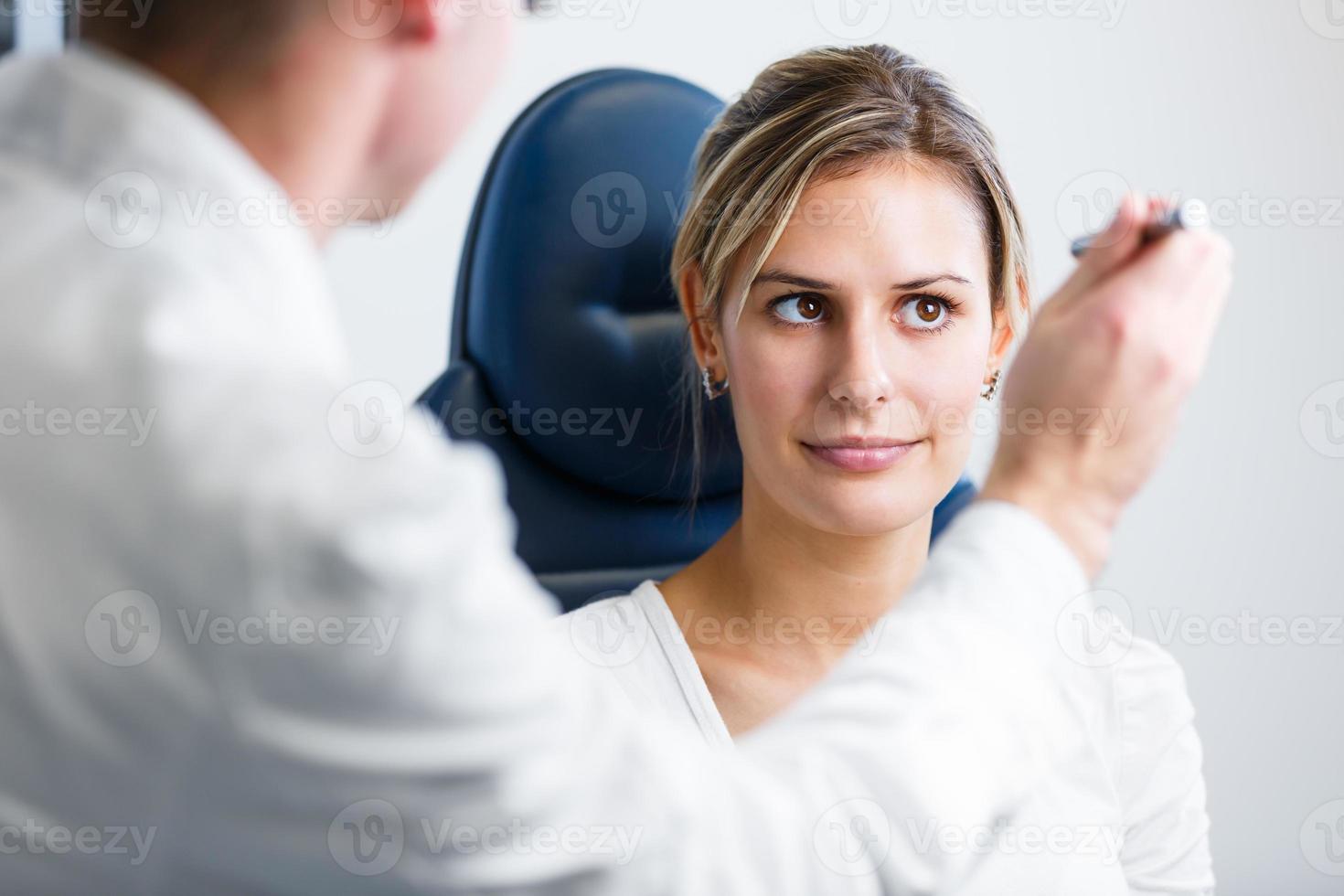 mooie jonge vrouw met haar ogen onderzocht door optometrie foto
