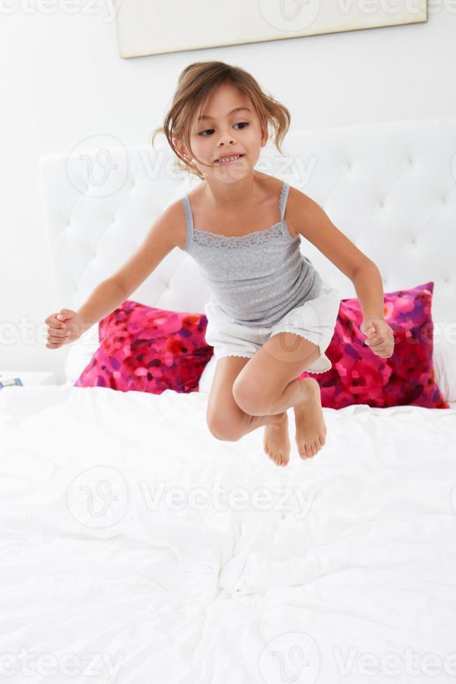 meisje springen op bed met pyjama foto