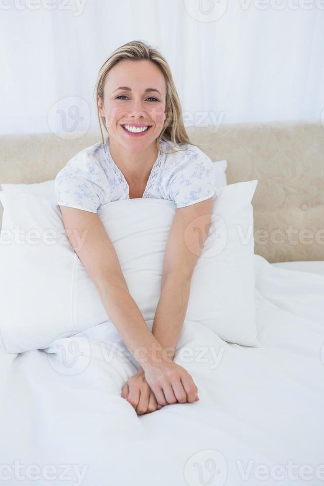 lachende blonde ontspannen in bed foto