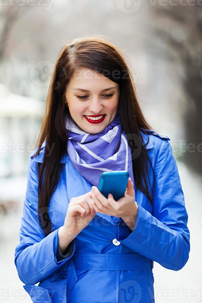 vrouw in jas met smartphone foto