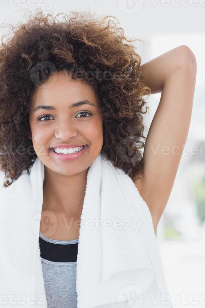 sportieve vrouw hand uitrekken achter terug in fitness-studio foto