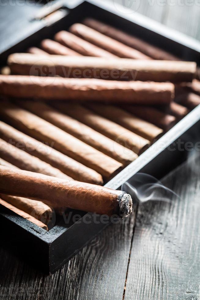 rook stijgt uit een brandende sigaar op houten humidor foto
